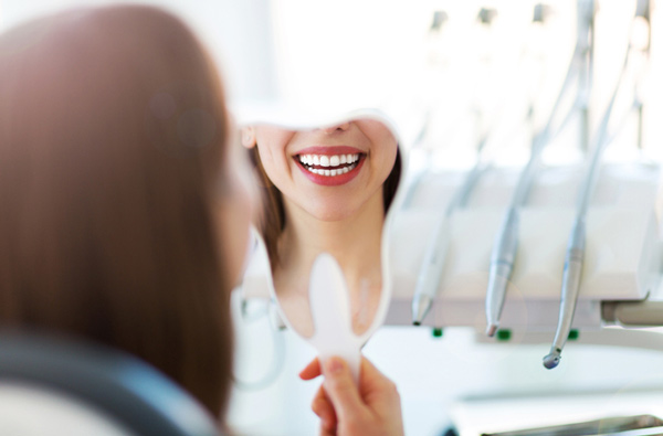 Woman looking at her smile in a mirror after restorative treatment at City Smiles DC
